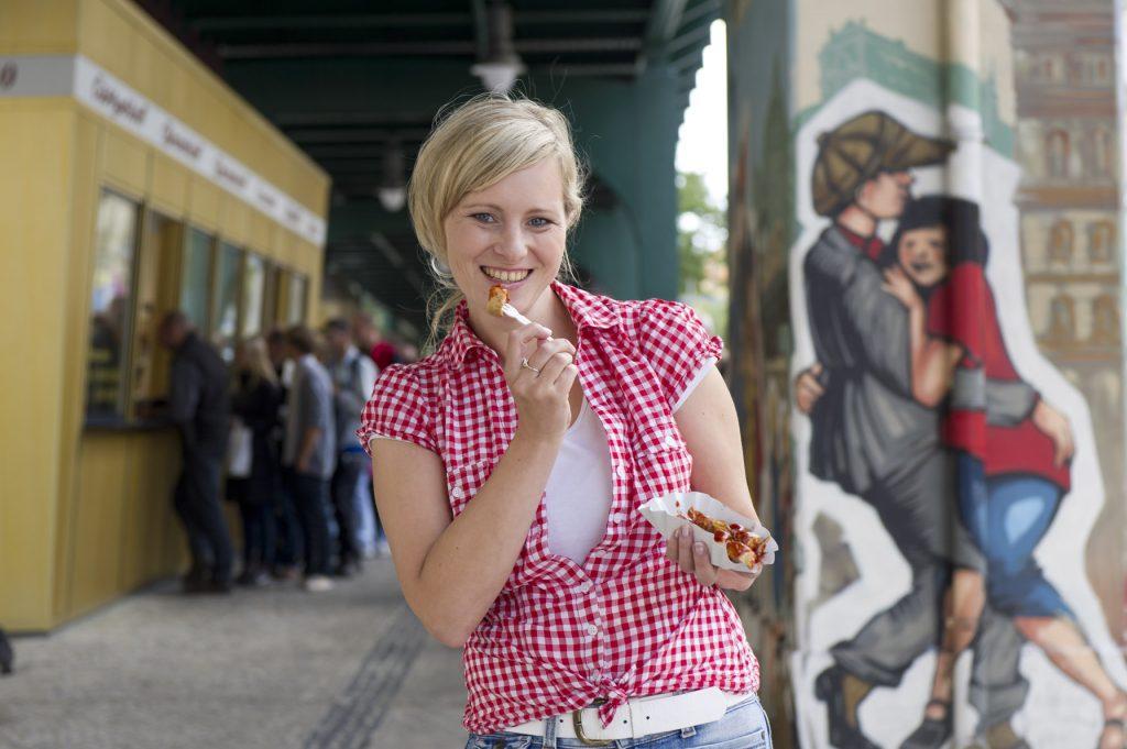 """فتاة تأكل نقانق """"كاري فورست"""" الشهيرة في حي برينتسلاور بيرغ في برلين"""